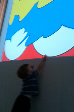 A child reaching up to one of Adi Da's art works